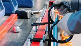 Lavoratore che fa assemblea manuale delle componenti del metallo sull'unità industriale stock footage