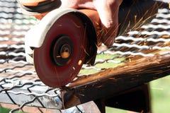 Lavoratore che frantuma una parte di metallo Fotografia Stock