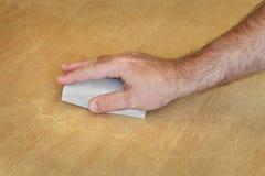 Lavoratore che insabbia plancia di legno, primo piano della mano Immagini Stock