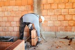 Lavoratore che installa la muratura del mattone sulla parete interna con il coltello di mastice della cazzuola immagini stock libere da diritti