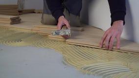 Lavoratore che installa parquet di legno stock footage