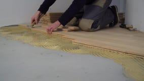 Lavoratore che installa parquet di legno Installazione rinnovata della stanza del parquet video d archivio