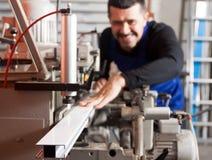 Lavoratore che lavora duramente su una macchina nella fabbrica del PVC fotografie stock libere da diritti