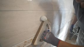 Lavoratore che mette fuga sulla parete nella cucina Riempire di malta delle mattonelle stock footage