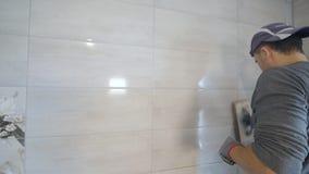 Lavoratore che mette fuga sulla parete nella cucina Riempire di malta delle mattonelle archivi video