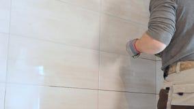 Lavoratore che mette fuga sulla parete nella cucina Riempire di malta delle mattonelle video d archivio