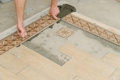 Lavoratore che mette le mattonelle sul pavimento immagine stock