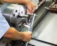Lavoratore che misura metro ny di giro della parte di CNC il micro Immagine Stock Libera da Diritti