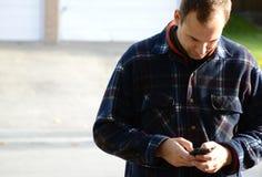 Lavoratore che per mezzo del telefono cellulare Fotografia Stock