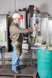 Lavoratore che per mezzo della macchina di CNC fotografie stock libere da diritti