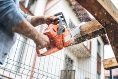 Lavoratore che per mezzo di una motosega industriale per il taglio del legno del legname al cantiere Fotografie Stock Libere da Diritti