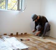 Lavoratore che pone parquet in una stanza Immagine Stock Libera da Diritti
