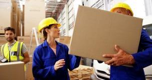 Lavoratore che porta una scatola e che interagisce archivi video