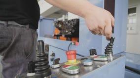 Lavoratore che preme i bottoni sul comitato per il controllo della macchina di CNC in fabbrica video d archivio