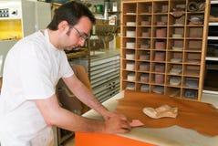 Lavoratore che prepara i sottopiedi ortopedici per un paziente sul suo worksho Fotografia Stock Libera da Diritti