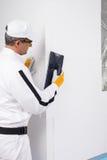 Lavoratore che raspa gli angoli dei pannelli dell'isolamento Fotografie Stock