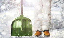 Lavoratore che rimuove neve sul cortile con la pala durante le precipitazioni nevose Immagini Stock Libere da Diritti