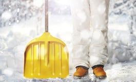 Lavoratore che rimuove neve sul cortile con la pala durante le precipitazioni nevose Fotografie Stock