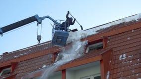 Lavoratore che rimuove neve sul tetto della costruzione archivi video