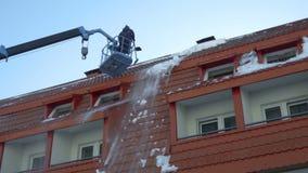 Lavoratore che rimuove neve sul tetto della costruzione video d archivio