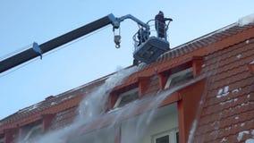 Lavoratore che rimuove neve sul tetto della costruzione stock footage