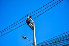 Lavoratore che ripara lavoro sul palo di potere elettrico della posta Immagine Stock