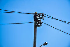 Lavoratore che ripara lavoro sul palo di potere elettrico della posta Fotografia Stock