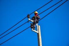 Lavoratore che ripara lavoro sul palo di potere elettrico della posta Immagini Stock