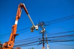 Lavoratore che ripara lavoro sul palo di potere elettrico della posta Fotografie Stock
