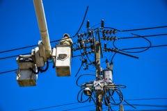 Lavoratore che ripara lavoro sul palo di potere elettrico della posta Fotografie Stock Libere da Diritti