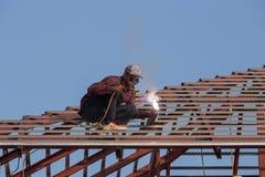 Lavoratore che salda l'acciaio per costruire il tetto Immagini Stock