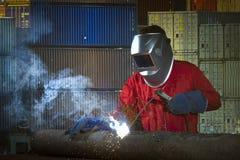 Lavoratore che salda la struttura del tubo d'acciaio fotografia stock libera da diritti