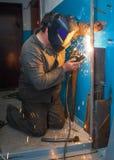 Lavoratore che salda una porta del metallo Fotografia Stock Libera da Diritti