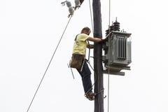 Lavoratore che scala sulla linea di trasmissione concreta elettrica del palo Immagini Stock Libere da Diritti