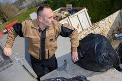 Lavoratore che scarica le borse dei rifiuti Fotografie Stock