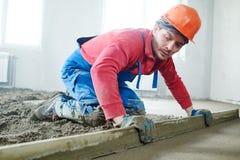 Lavoratore che screeding il pavimento dell'interno del cemento con la tirata fotografia stock