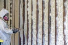 Lavoratore che spruzza l'isolamento chiuso della schiuma dello spruzzo delle cellule su una casa immagine stock libera da diritti
