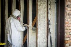 Lavoratore che spruzza l'isolamento chiuso della schiuma dello spruzzo delle cellule su una parete domestica fotografie stock