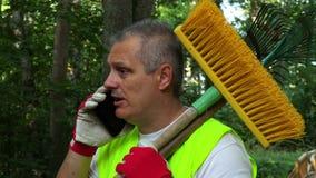 Lavoratore che tiene gli strumenti sulla spalla e che per mezzo dello smartphone