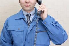 Lavoratore che tiene un microtelefono fotografia stock libera da diritti