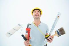 Lavoratore che tiene varia attrezzatura sopra fondo bianco Fotografia Stock