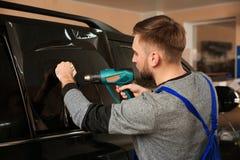 Lavoratore che tinge la finestra di automobile con la pistola di calore fotografie stock