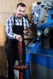 Lavoratore che utilizza gli strumenti nell'officina di riparazione degli stivali Immagini Stock