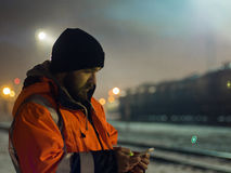 Lavoratore che utilizza smartphone nella penombra Concetto del turno di notte fotografia stock libera da diritti
