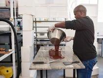 Lavoratore che versa cioccolato artigianale fuso fuori su una tavola della fabbrica fotografie stock