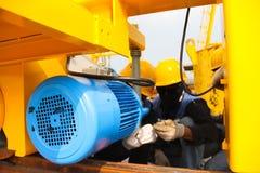 Lavoratore circa il motore elettrico Fotografia Stock