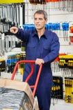 Lavoratore con il carrello che indica nel negozio dell'hardware Immagine Stock Libera da Diritti