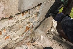 Lavoratore con il martello elettrico che pulisce muro di mattoni rosso Fotografie Stock Libere da Diritti