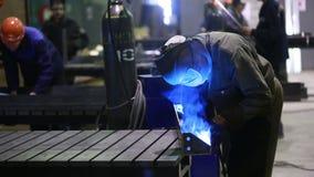 Lavoratore con il metallo di saldatura della maschera protettiva stock footage