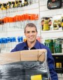Lavoratore con il pacchetto avvolto nel negozio dell'hardware Immagini Stock